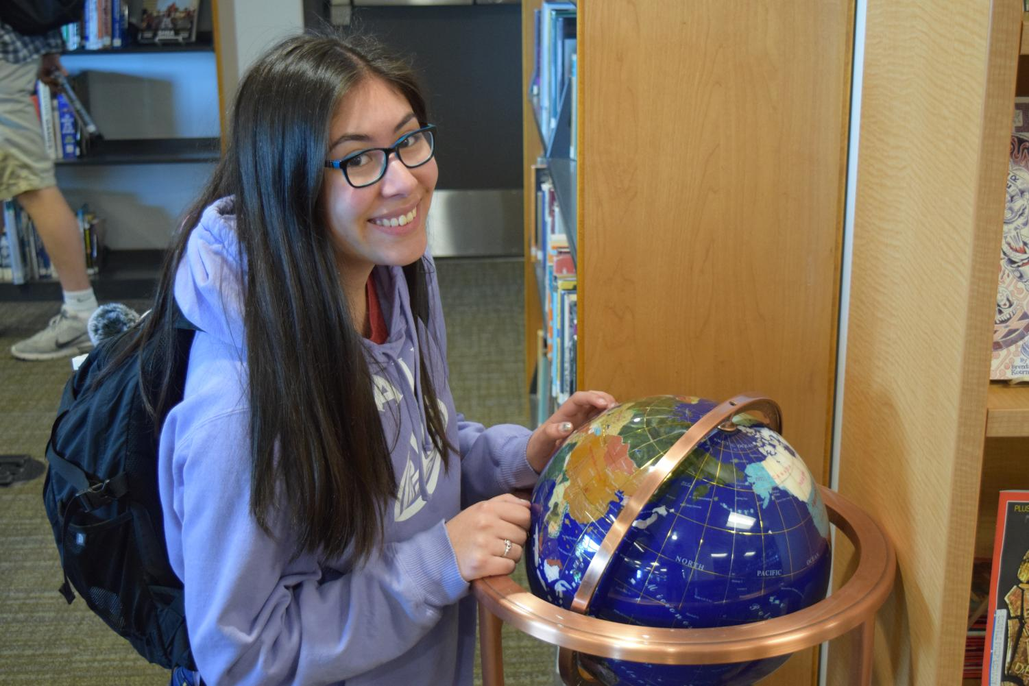 Ganz poses with a globe as she sets sights for her future voyages during her gap year.