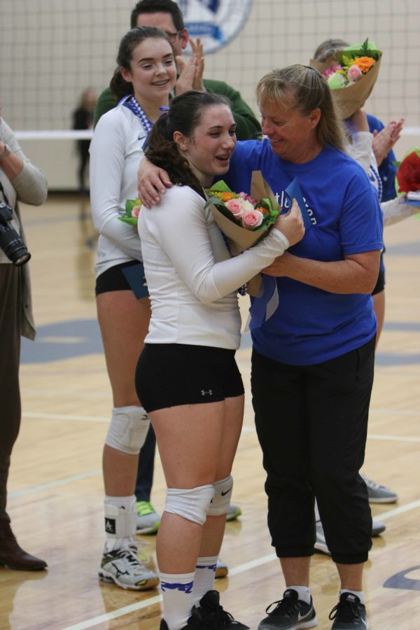 Sierra Leza '17 receives flowers and a hug from Coach Sullivan during the Girls Volleyball Senior Night ceremony. Senior Night coincided with Girls' Night Out, a tradition celebrating girls sports throughout Seattle Prep.