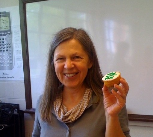 The math teacher poses with a pi-themed cupcake made by a student.