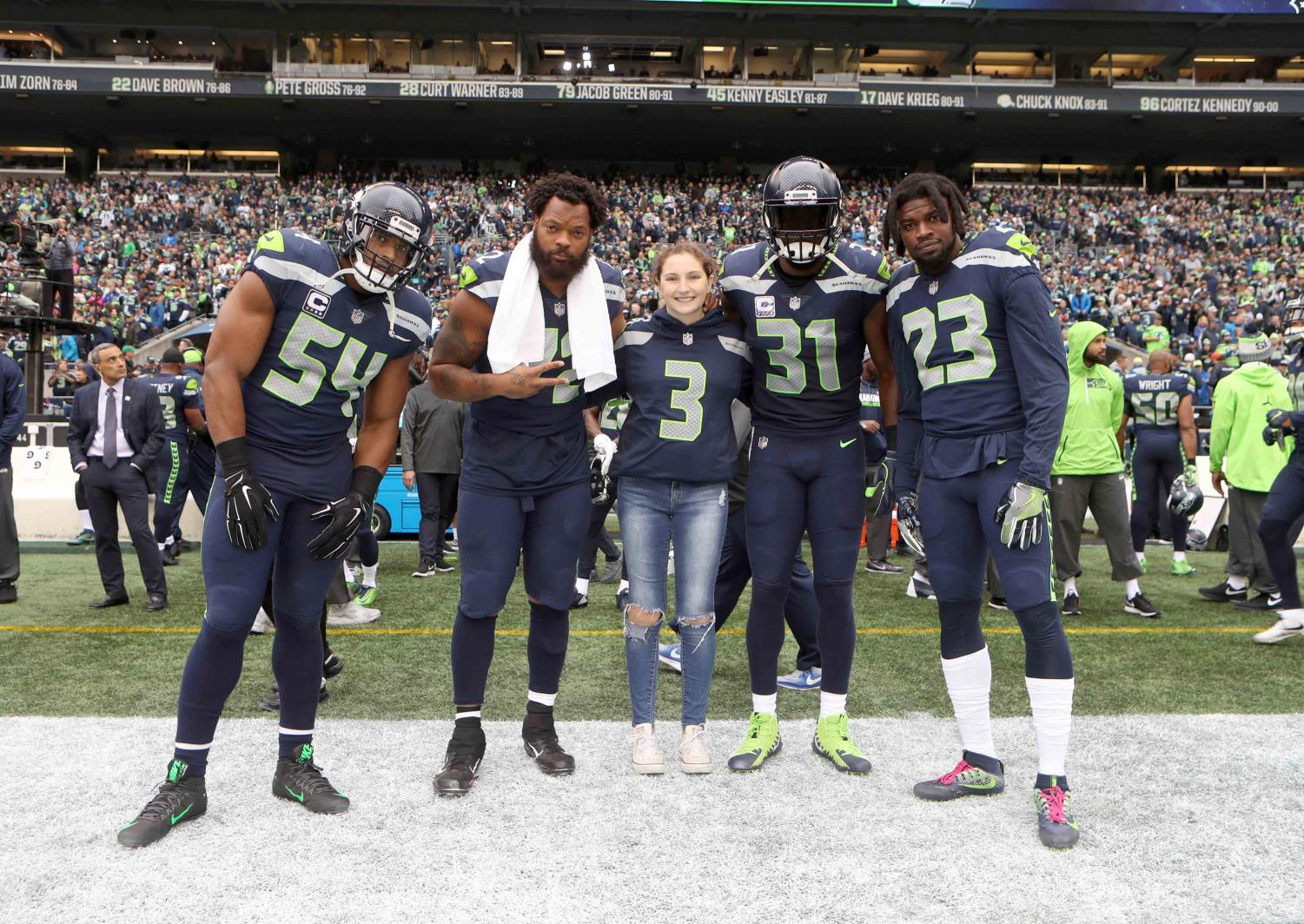 Senior Bridget Howard poses with Seahawks Players Bobby Wagner, Michael Bennett, Kam Chancellor and Neiko Thorpe. Howard was honored by the Seahawks as a part of their Crucial Catch campaign for cancer awareness.