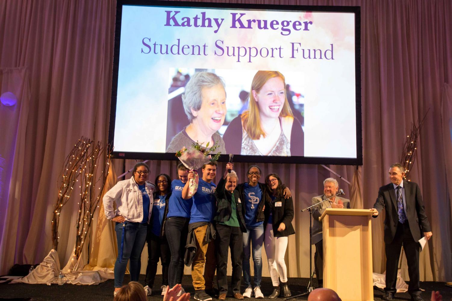 Mrs. Krueger celebrates the new Student Support Fund with students on stage at the auction. The fund is now named in Krueger's honor.