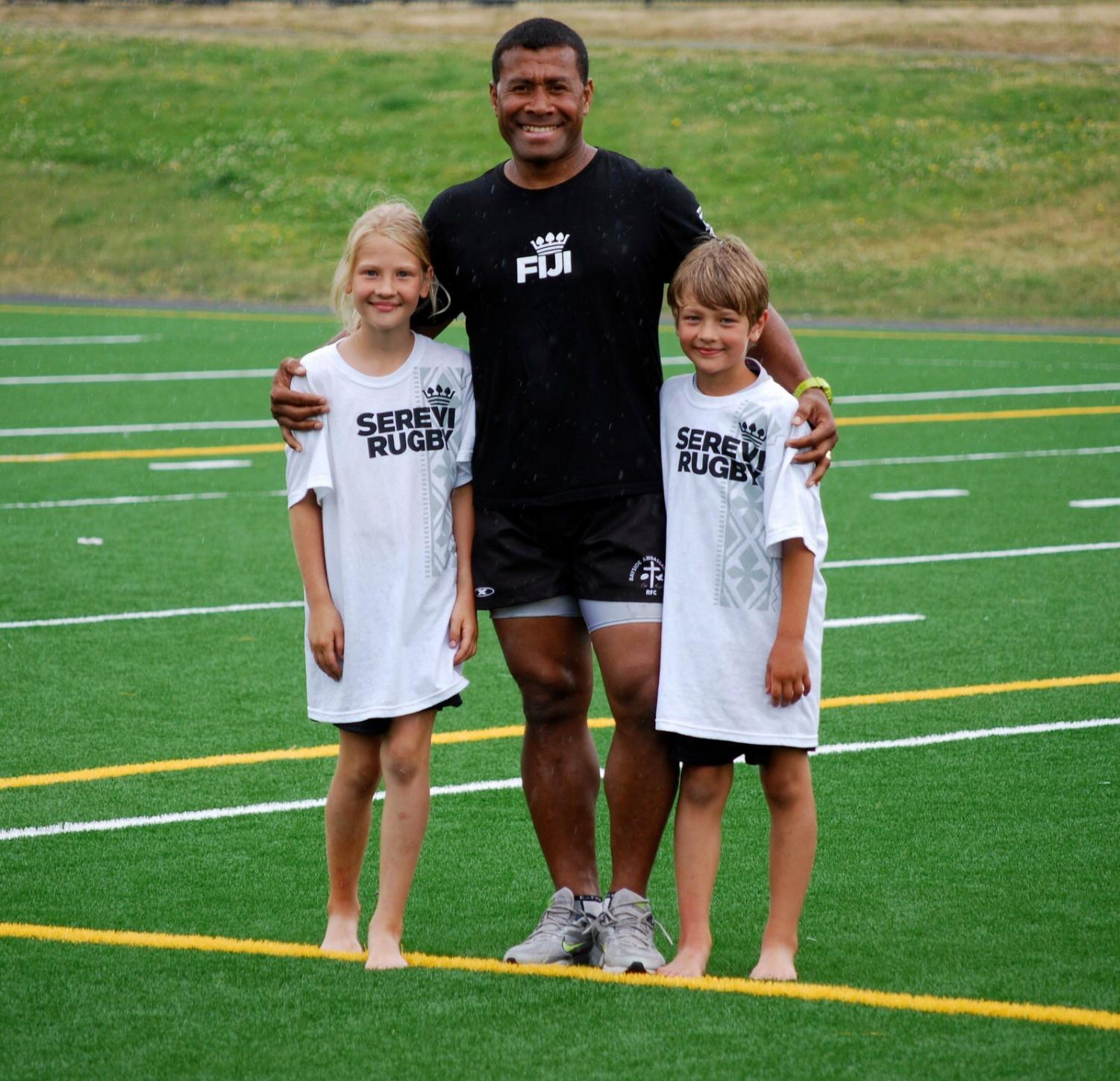 Chloe O'Meara and her younger brother, Kieran, posing with a Serevi Rugby player.