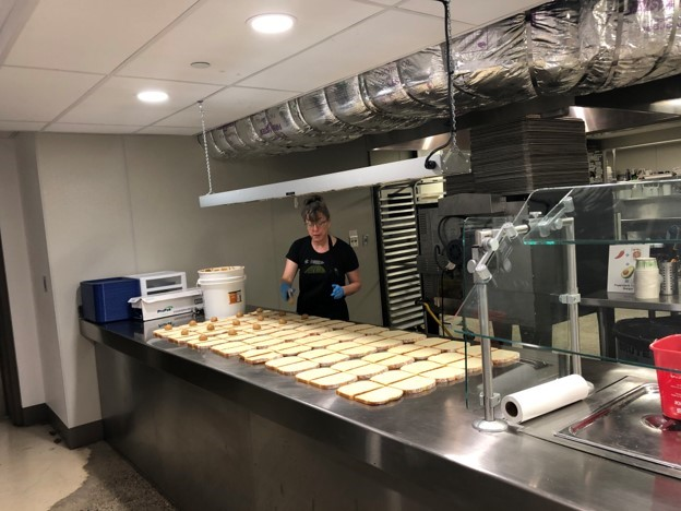 Smith Cafe Staff member Jannie Curtin prepares sandwiches for local Catholic School students.
