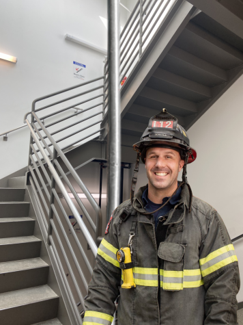 A Seattle Fire Department member poses following the final inspection of the new firepole installed in Adelphia Memorial Hall. The new firepole allows greater student freedom during passing periods.